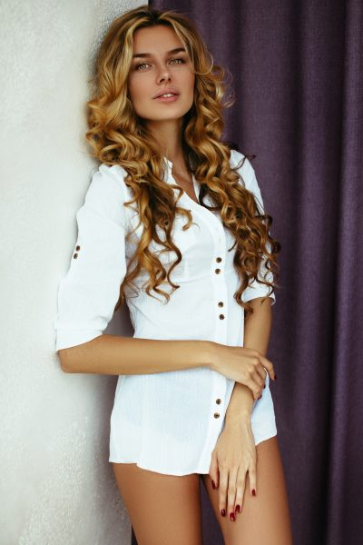 Beautiful blonde girl with long hair. With hair and makeup, posing in the morning in an apartment on the background of purple curtains in a white shirt. The light from the window, soft focus